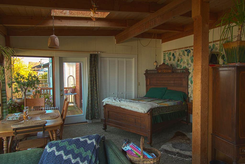 Antique spindle bed and dining area with balcony beyond.