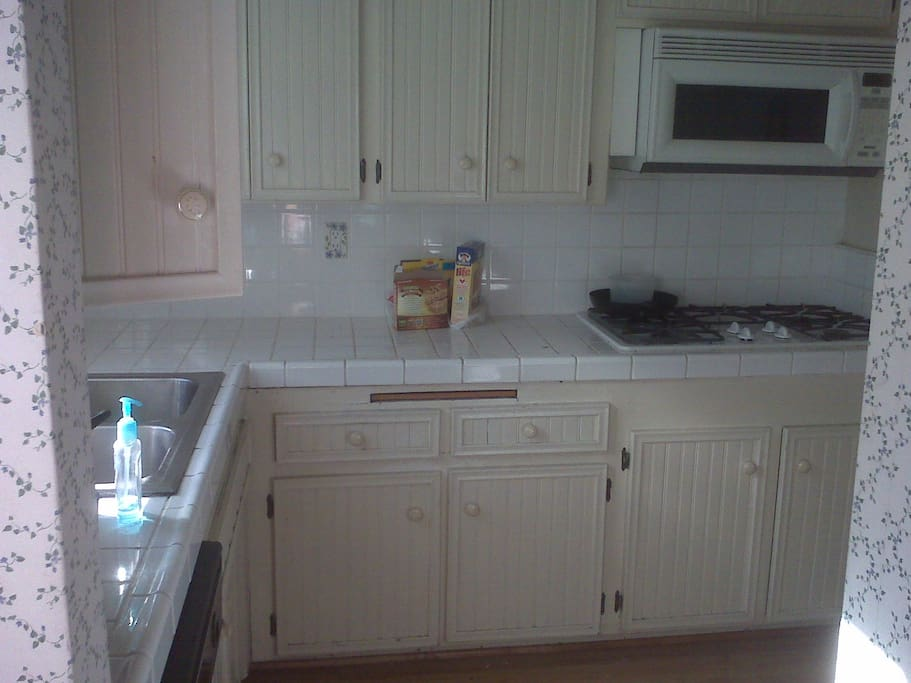 Shows full kitchen with all amenities - large fridge, plenty of countertop space and storage, all kitchenware, microwave, toaster oven, washing machine, double oven and stove top.