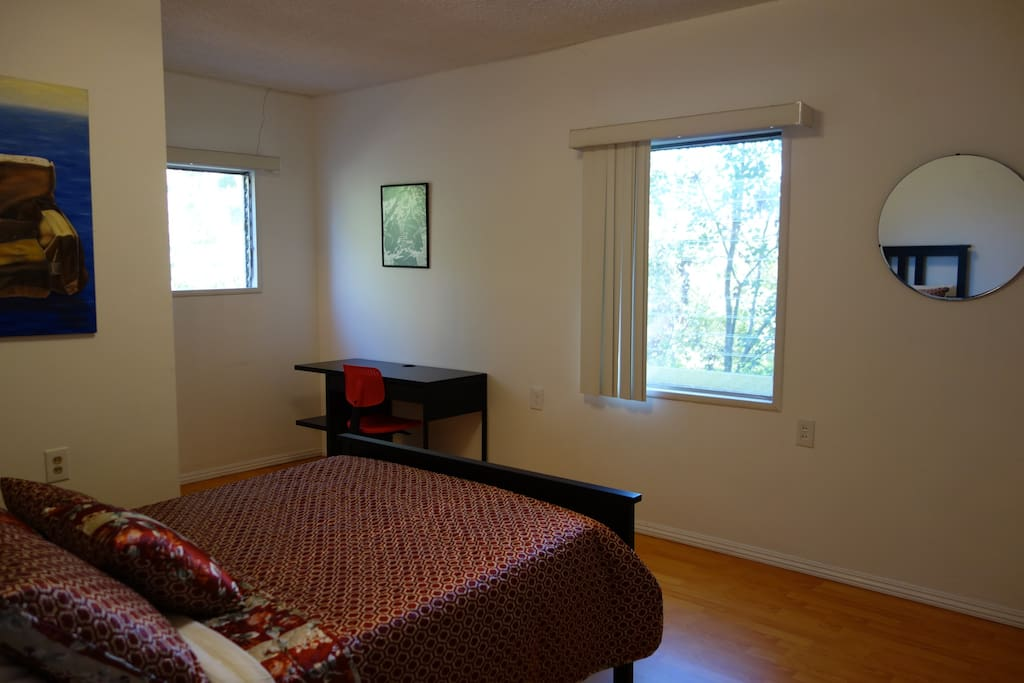 Spacious bedroom with desk, closet, and shared half-bath.