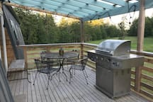 Outdoor covered seating area with propane grill.  The deck wraps around the south and west sides.