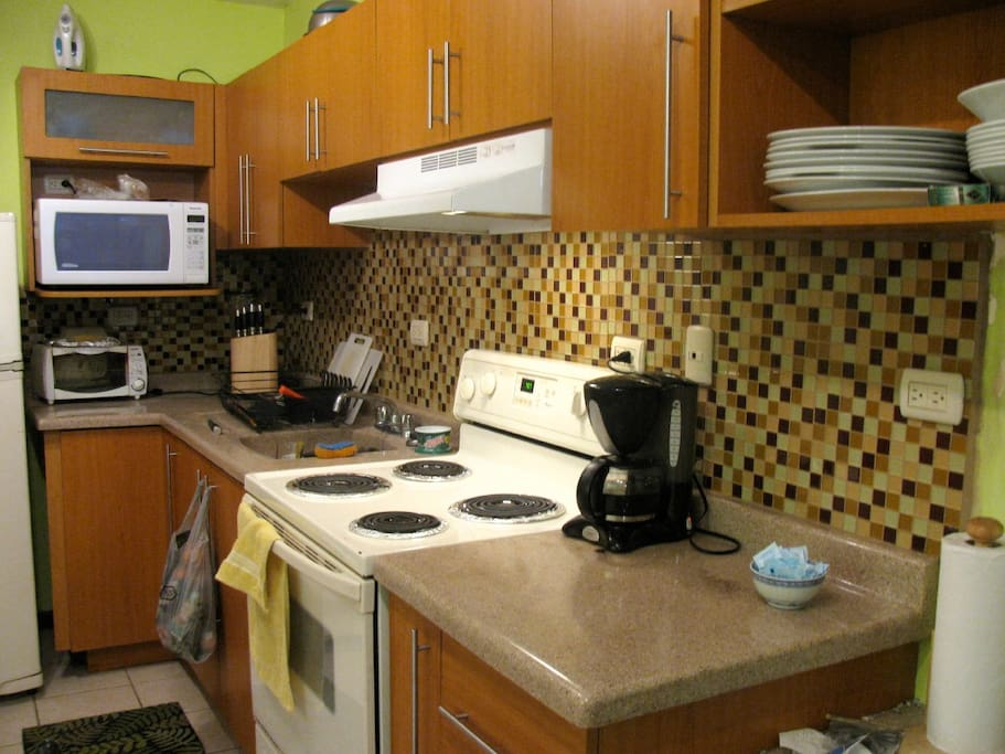 A fully equipped kitchen with nice pots and dishes