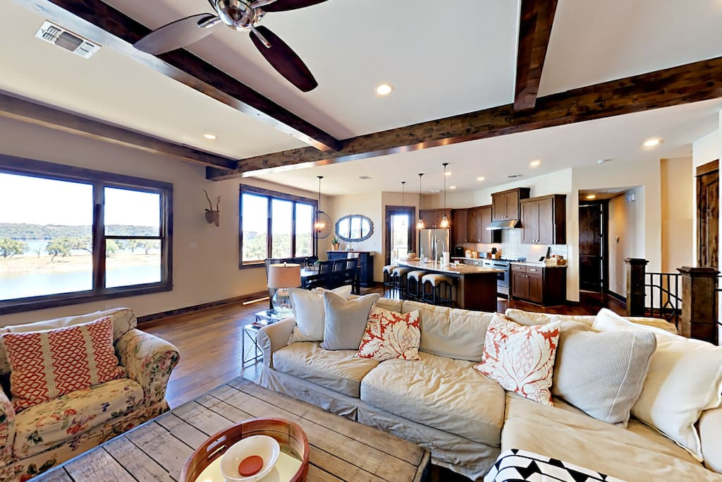 The living room with lake views flows into the kitchen to create an airy, open gathering space.