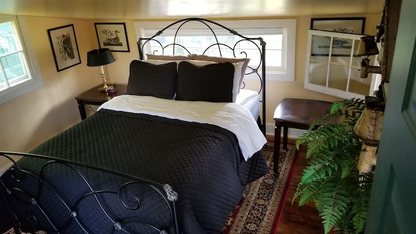 Queen sized bed that includes sheets, blanket, and pillows.