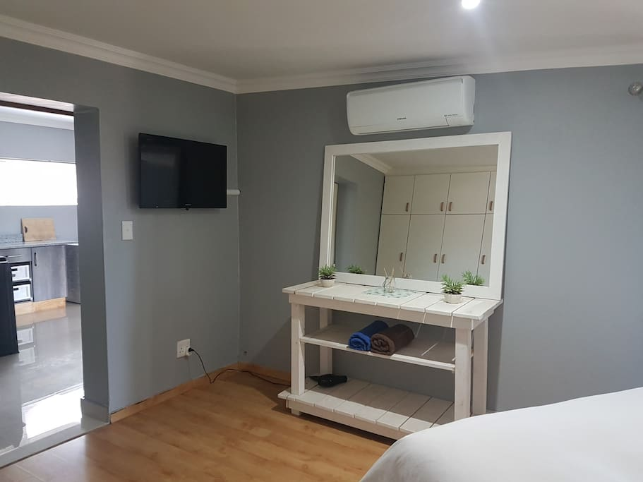 Main bedroom with dstv. Modern feel with air conditioning.