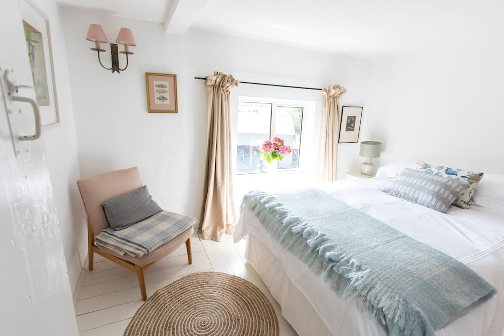 A south-facing double bedroom, with creamy warm colours and painted wooden floor.