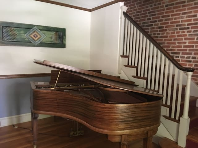 The living room doubles as a Music room with a tiger maple baby grand piano.