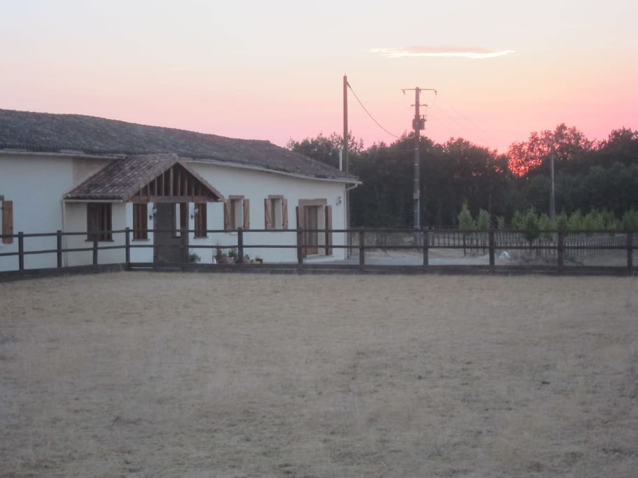 Sun set behind the house & horse sand arena.