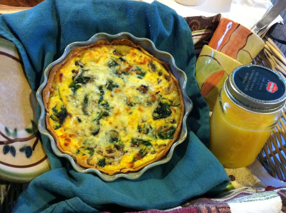 Mushroom spinach quiche  served in hostess-made pottery, with orange juice
