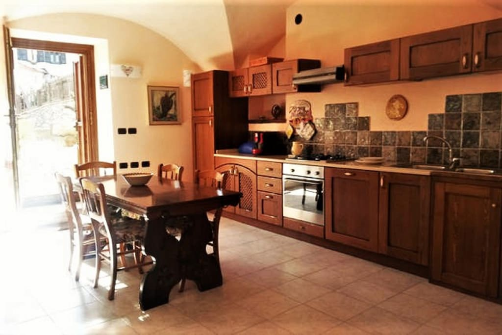 Cucina ampia e attrezzata con fuochi, forno, lavastoviglie, frigo e freezer, grande tavolo da pranzo