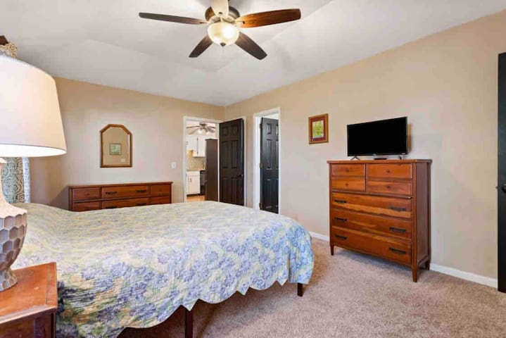 Master bedroom with a queen bed, two full sized dressers, two bed side tables, 2 closets attached, and a TV
