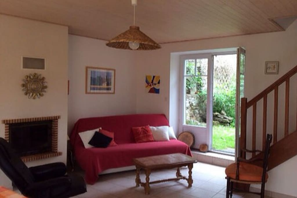 Le coin salon comporte un canapé-lit, une table basse et une cheminée avec insert.
