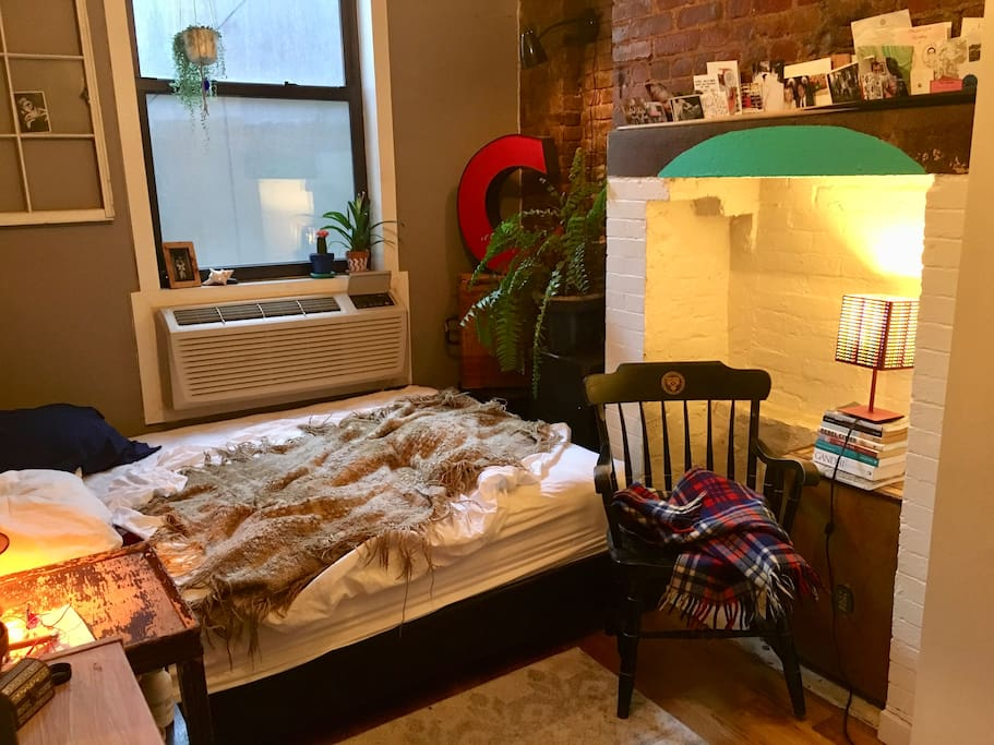 Here you see the bedroom window, the AC/heater, queen bed, the brick fireplace and a nice reading chair.