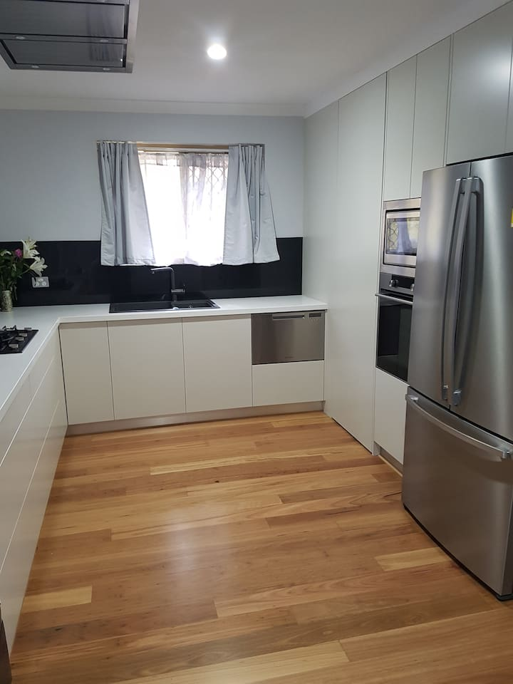 Shared modern fully equipped kitchen. Has extendable dining table in corner. Tea and coffee facilities in pantry. Guest storage in pantry and fridge.