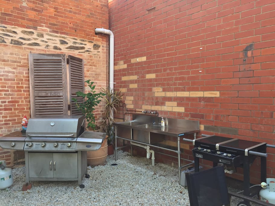 The fully enclosed, private garden boasts a BBQ area with large sinks and hot and cold taps, and a timber table and bench for several people.