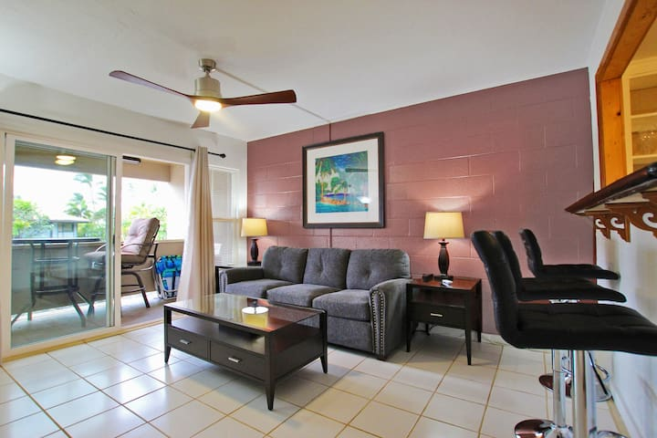 Living area features comfy sleeper sofa, air conditioner and ceiling fan, coffee tables, and tables and lamps, next to the balcony lanai
