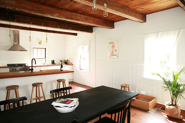 A fully renovated chef's kitchen and dining room with windows on all sides.