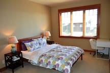 Lower level bedroom with a Queen bed, desk with chair, private bathroom and spectacular ocean views