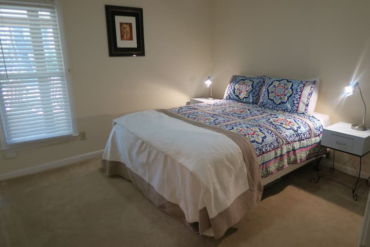 Bedroom with queen sized bed, walkin closet and on-suite bathroom.  Simply and cleanly decorated.
