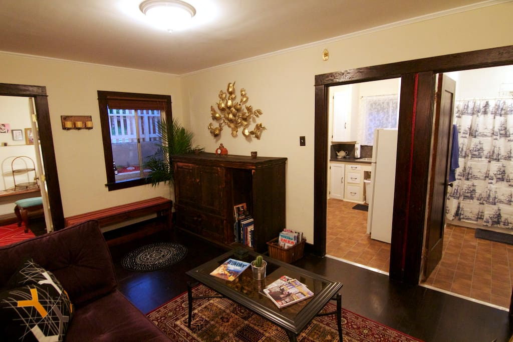 View of living room, bathroom, kitchen and back bedroom.