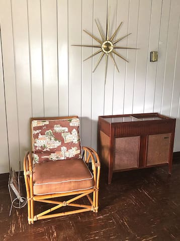 Living room, vintage Heywood-Wakefield chair, starburst clock, and record player