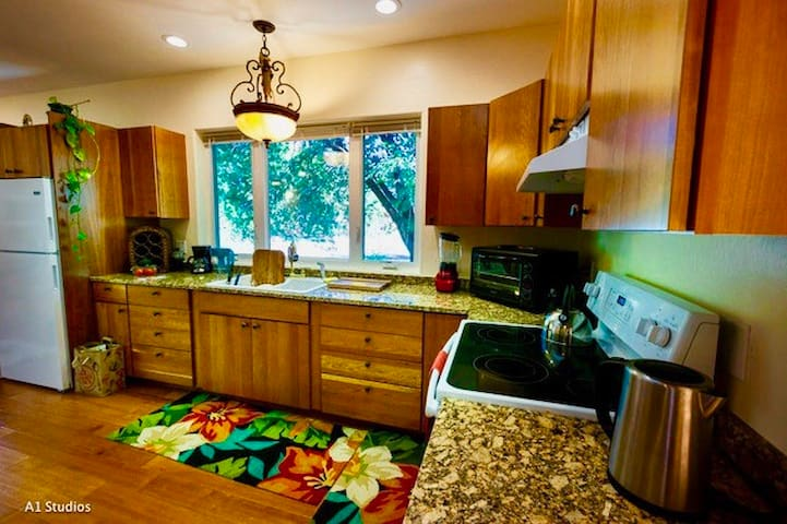 The kitchen's cherry cupboards are fully equipped. The granite counter tops match the natural granite cliffs from which this photo was taken.
