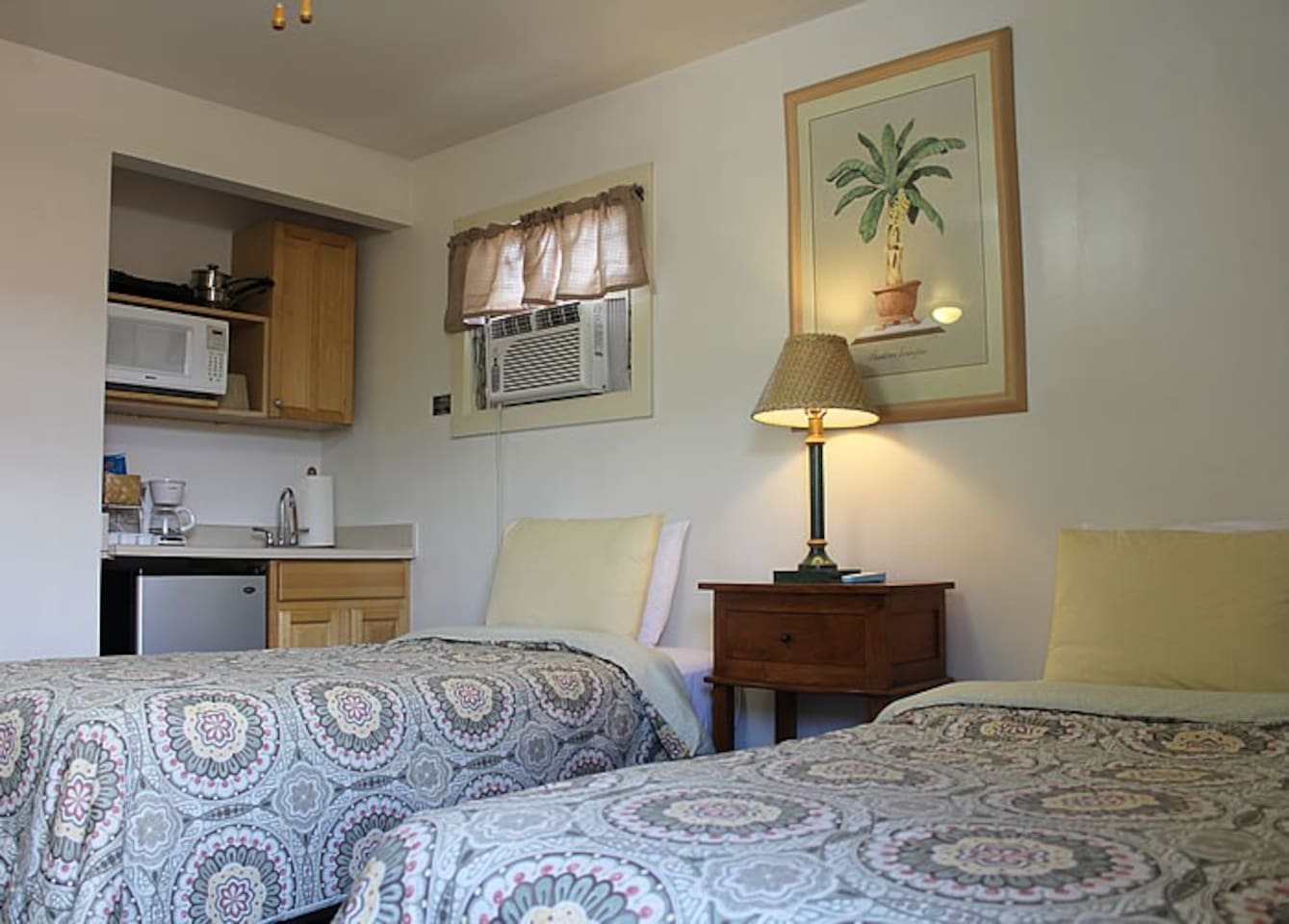 Deluxe room with a kitchenette unit, air conditioning, flat screen TV and mini fridge.