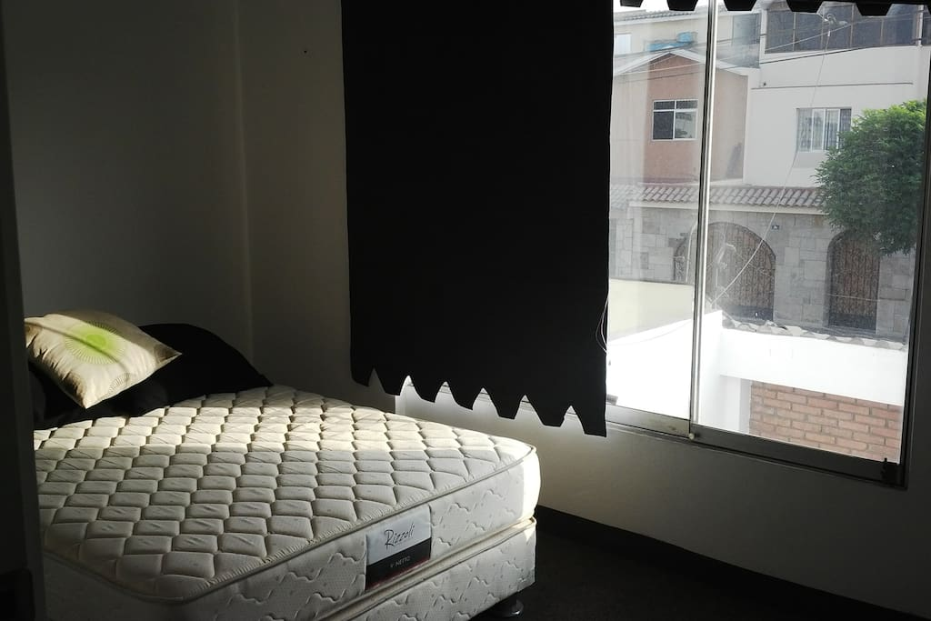 Dormitorio con cama queen size, vista a la calle. Alfombrado y con closets.