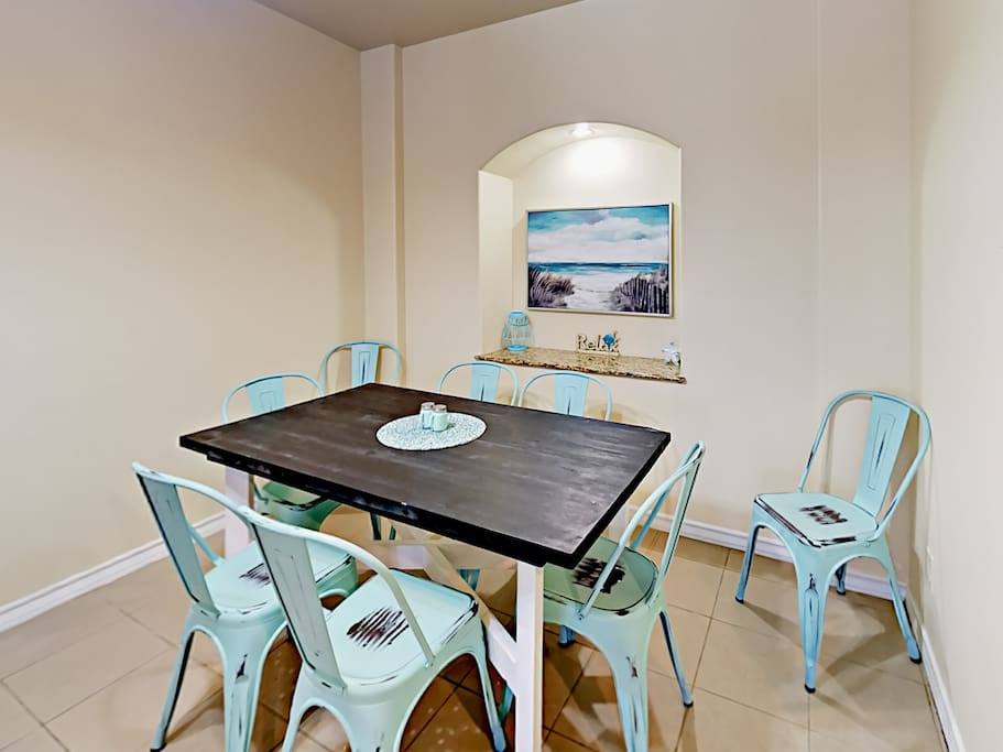 A beachy dining area has seating for 8.