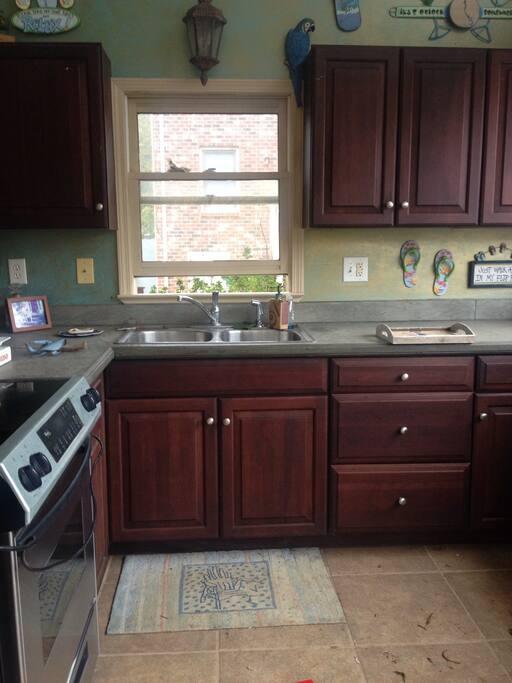 Outdoor kitchen has full size range,  mini refrigerator and 2 bin sink.