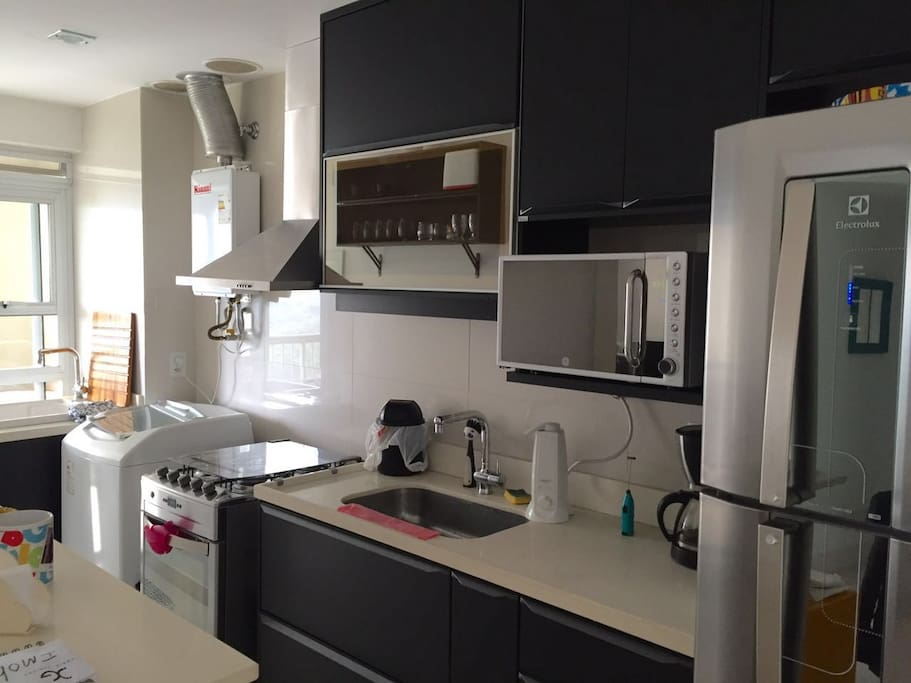 American Kitchen with access to the balcony, stainless Refrigerator, Microwave, cooker, fume cupboard, gas heater, washer, laundry sink, coffee machine, water filter, toaster, glasses, cutlery, dishes, pans and a lot of cabinets.