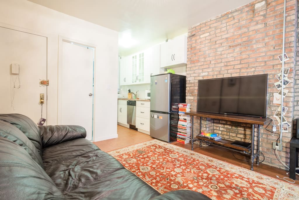 Large clean living room with brick exposure. Please note that the television is now smaller and on a different stand.
