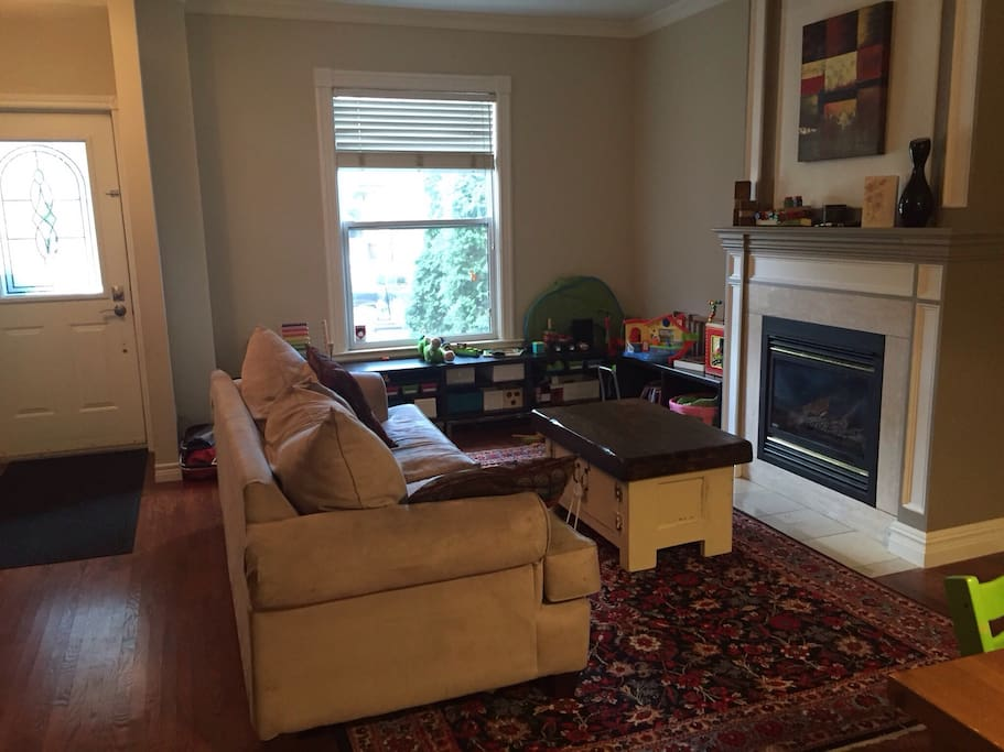 Bright living room with play area and gas fireplace.