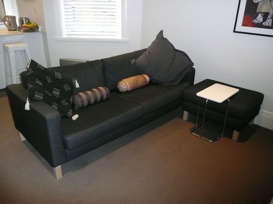 3 seater couch + foot stool in living room