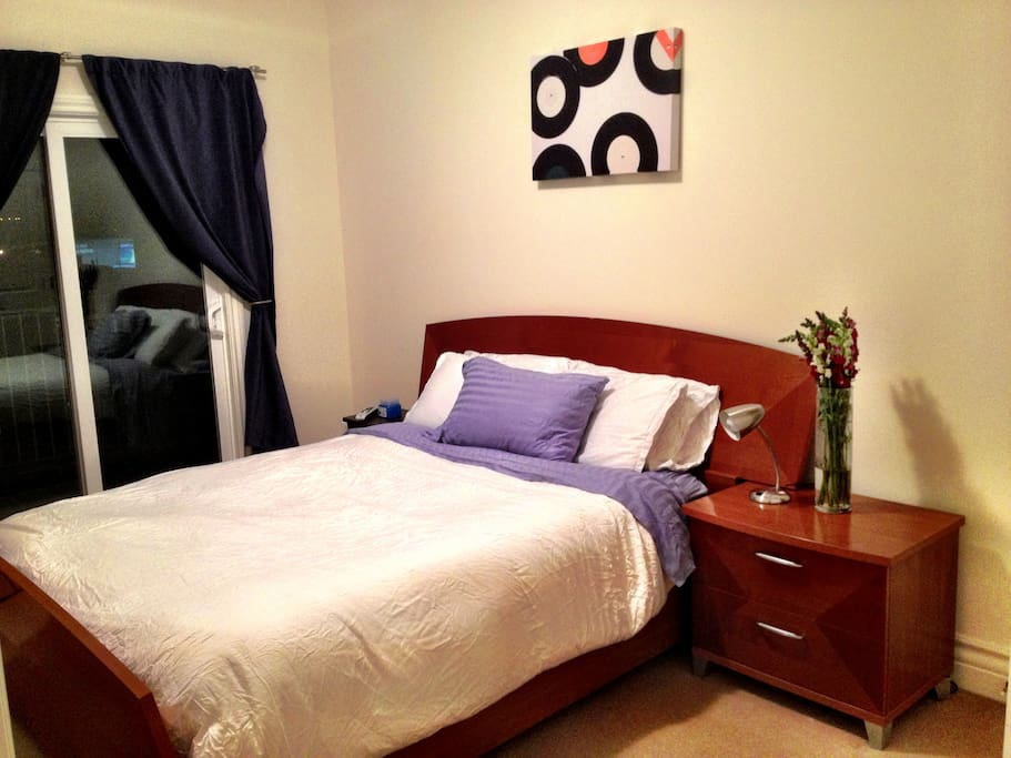 Comfortable master bedroom with queen bed and adjacent balcony