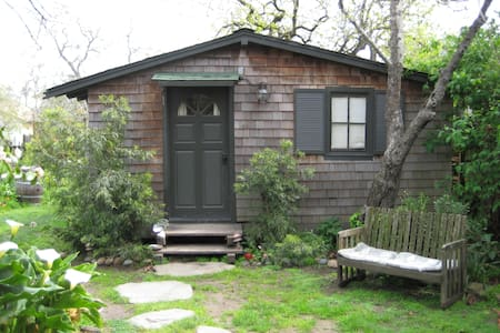 Our quiet guest cottage is well located in a cental residential area, walking distance to great restaurants, and a short bike ride to beach or downtown. Cute bathroom with unique shower, modern efficiency kitchen, cozy gas fireplace. Have coffee on the patio under the trees!