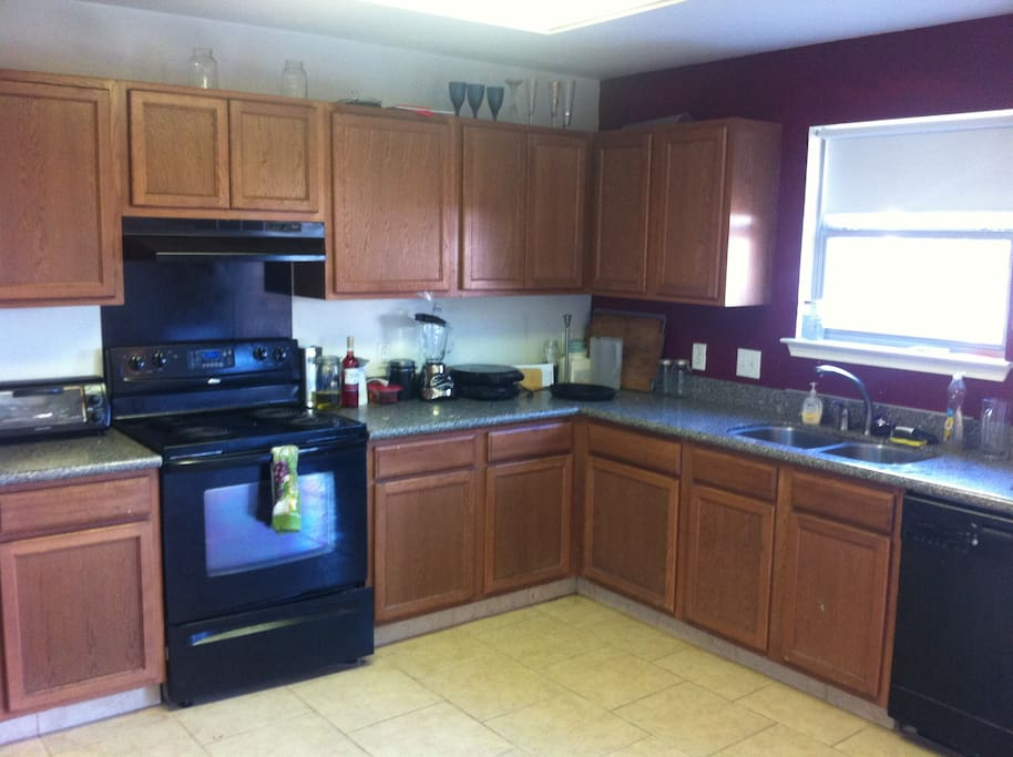 Huge Kitchen with Stainless Steel Refrigerator, Plenty of dishes, oven, microwave, and extra freezer.