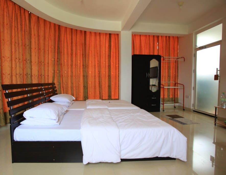 Deluxe Bedroom with AC, TV, and Mini Fridge.