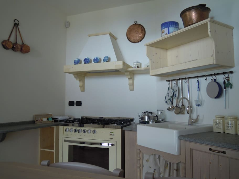 The kitchen equipment: a stove with 5 hobs electric, oven, microwave, kettle, toaster