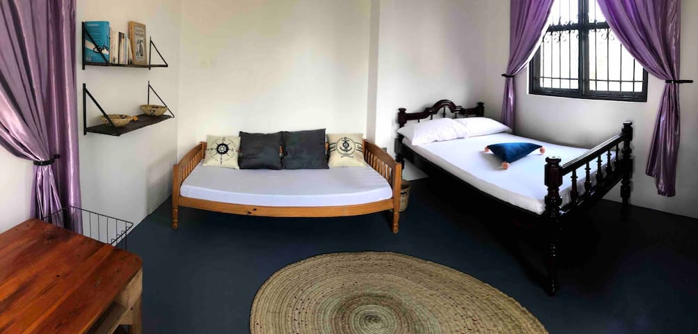 Panoramic photo of the room. One single bed that can be used as a sofa and one small double bed. All beds are provided with mosquito nets as well as all windows.
