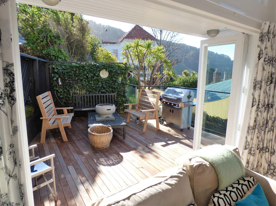 Private sunny sheltered deck of sitting room with view of city