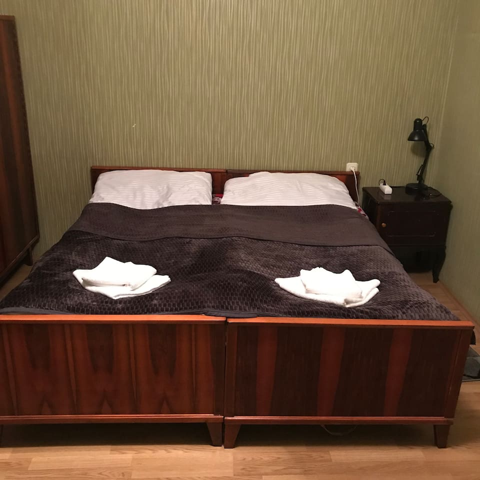 Bedroom with 2 beds, 1 sofa, wardrobe, pump, small table and chair.