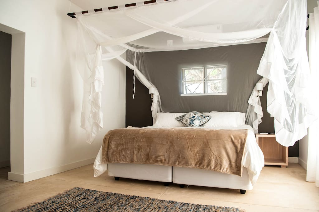 a bright and sun-lit  air-conditioned bedroom boasting crisp white linen and 5-star quality bed