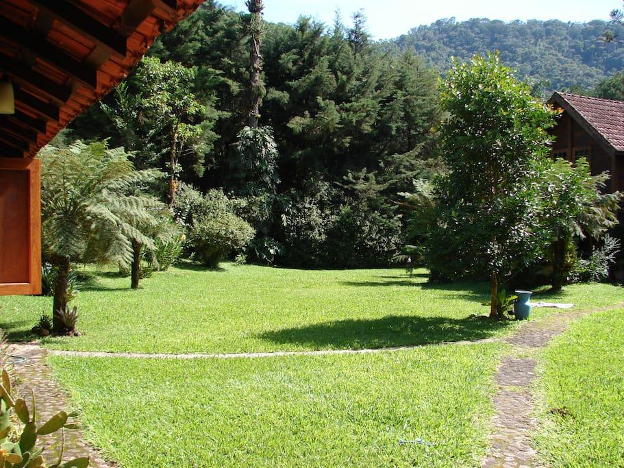 Visão da cama de casal para o terreno onde o chalé está localizado.