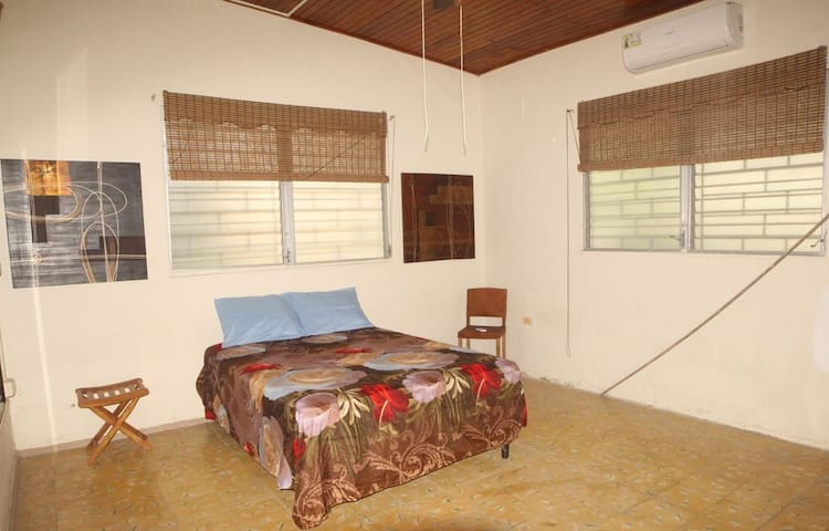 Master bedroom with double bed, AC, and closet space