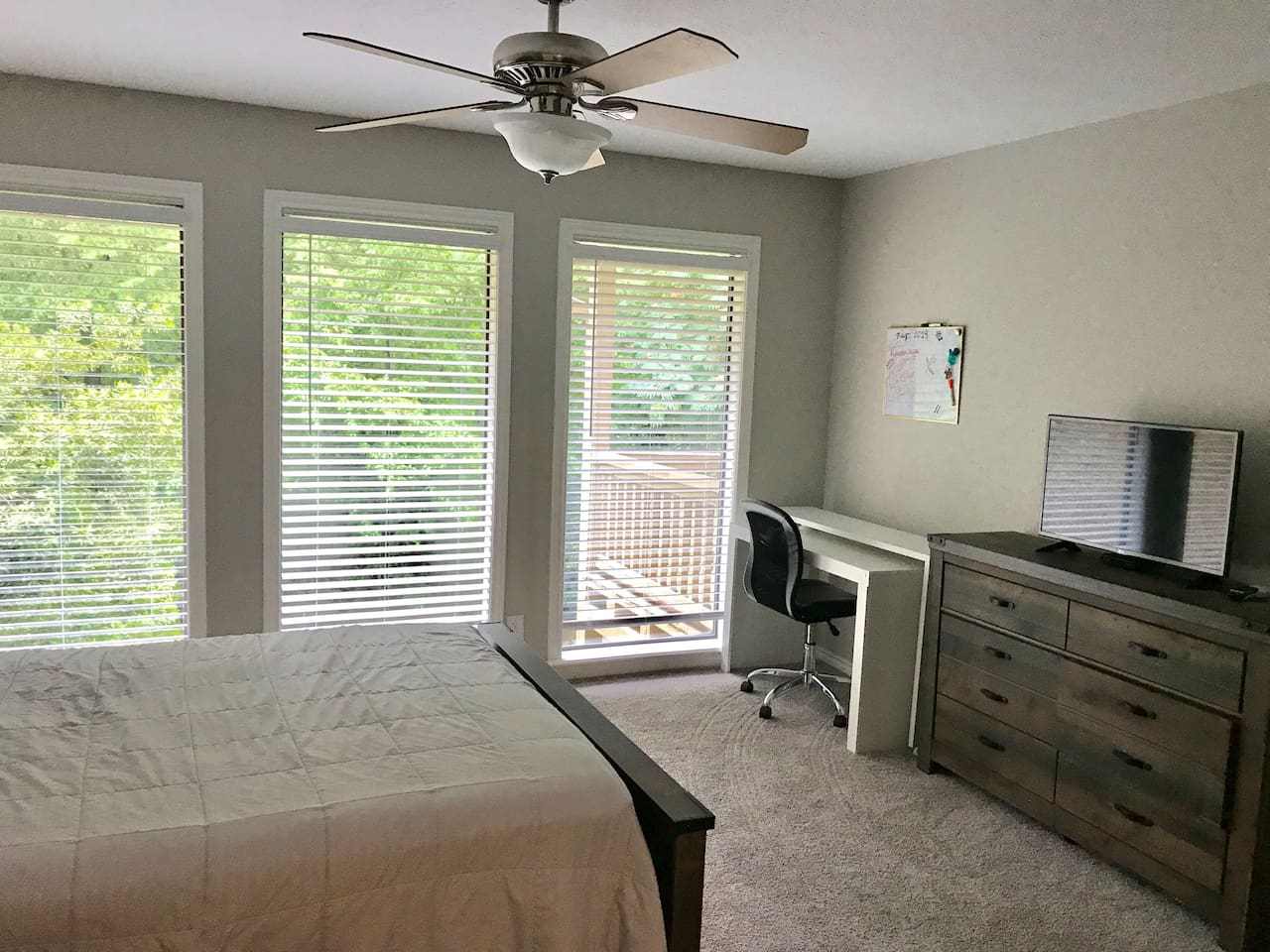 This bedroom overlooks the backyard with 3 big windows. It has a desk with TV.