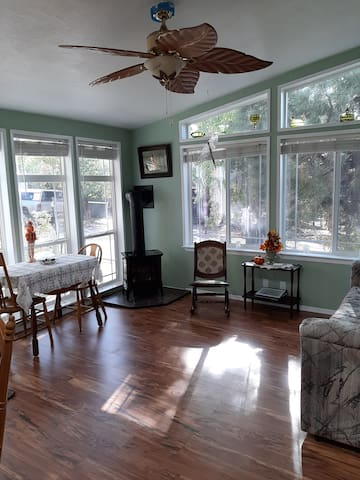 Living room with ceiling fan and propane stove that is on a thermostat.  A table that can fold out to seat 4 people.   Lots of east facing windows to view the sunrise.