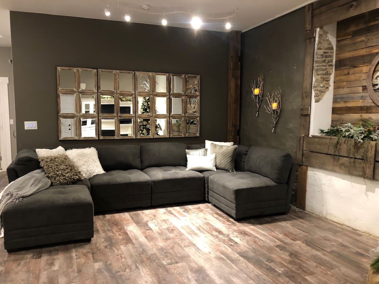 Large but cozy living area.  Vintage beams are wall mounted behind the sectional for drinks, phone or laptop charging  etc...