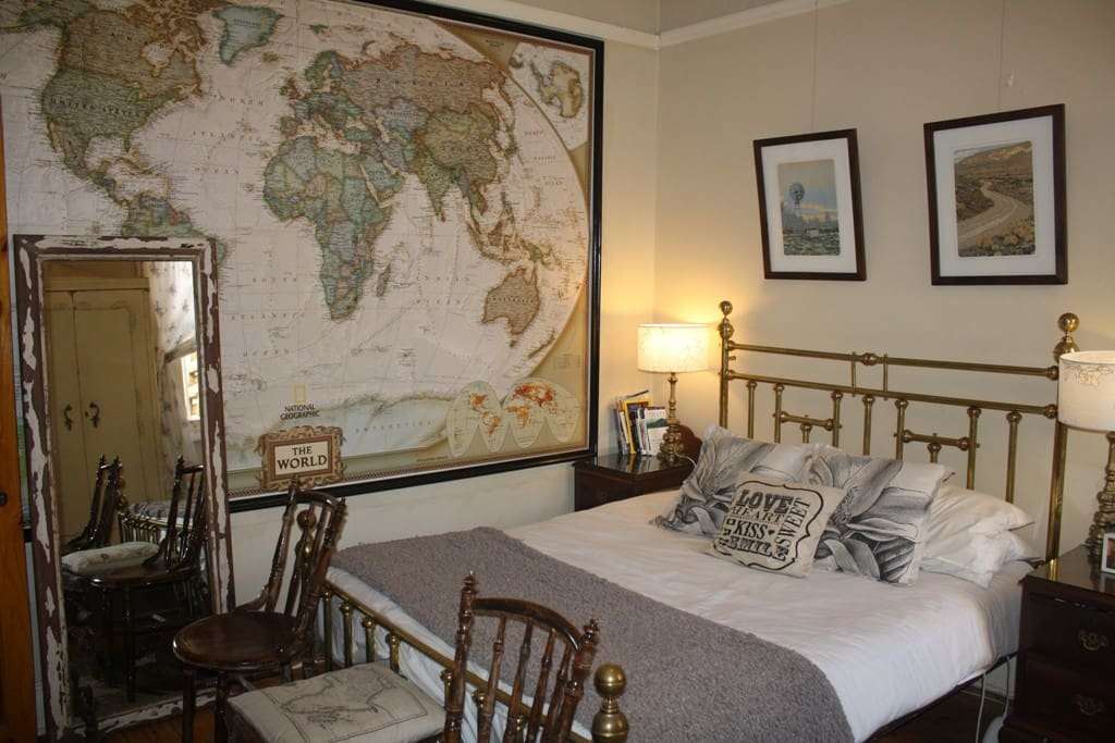 Queen bedroom, lovely brass bed bolted to the wall, with giant wall map