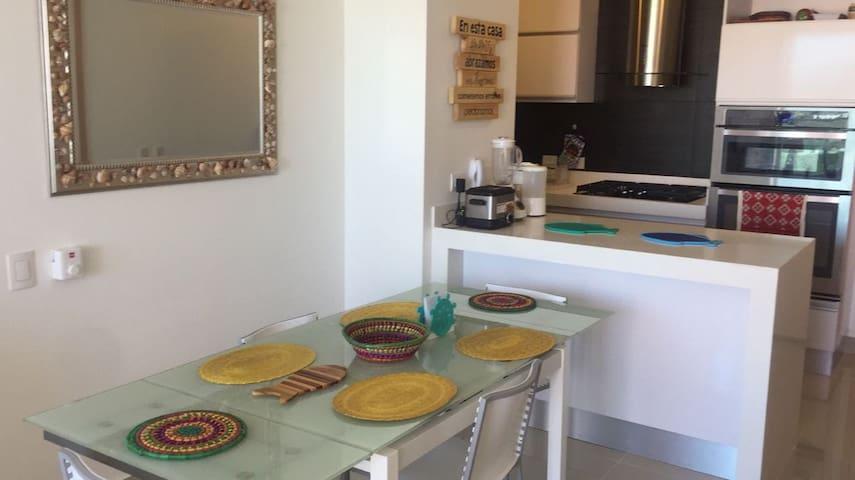 Dinning table & kitchen on the back / Comedor y cocina al fondo.