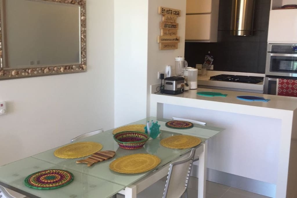Dinning table & kitchen on the back / Comedor y cocina al fondo.